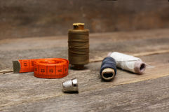 Thimble and spools of thread on an aged wooden surface Stock Photos