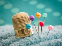 Thimble, straight pins and pin cushion. A few basic items essential for hand sewing: thimble, straight pins and a pin cushion Royalty Free Stock Image