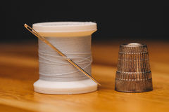 Thimble and thread with needle on table Stock Photo