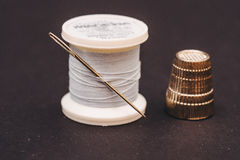 Thimble and thread with needle on table Royalty Free Stock Images