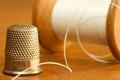 Thimble and thread Stock Photo