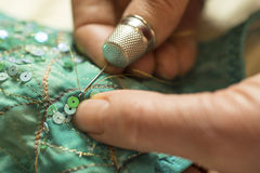 Thimbled Thumb Pushing Needle with Gold Thread Through Garment Stock Images