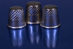 Thimbles. Three thimbles on a blue table Royalty Free Stock Photography