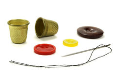 Thimbles, color buttons and needle for sewing on a white background Royalty Free Stock Photos