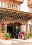 Thimphu Bhutan - September 10, 2016: Bhutanesisk vakt för kunglig slott med lokala kvinnor som står på byggnadsingången Arkivfoto