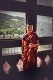 Thimphu, Bhutan - 10. September 2016: Buddhistischer Mönch des jungen Anfängers in den Roben der rötlichen Orange, die vor einem  Lizenzfreie Stockfotos