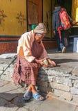 Thimphu Bhutan - September 16, 2016: Gammal bhutanesisk kvinna som framme sitter av hennes hus och knäcker muttrar med en sten Arkivbild