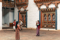 Thimphu, Bhutan - September 10, 2016: Local Bhutanese people wearing traditional clothing standing in the backyard of the temple. Royalty Free Stock Photography