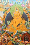 Thimphu Bhutan - September 11, 2016: Måla föreställa den gula Dzambhalaen som rymmer den spouting mungor för juvel, Bhutan Royaltyfria Foton