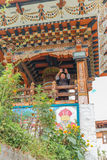 Thimphu Bhutan - September 15, 2016: Sikten för den låga vinkeln av en lycklig munk framme av bönen rullar in Simtokha Dzong, Thi Arkivbilder