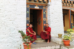 Thimphu, Bhutan - September 15, 2016: Two smiling young monks sitting in front of the door in Simtokha Dzong, Thimphu, Bhutan Royalty Free Stock Photos