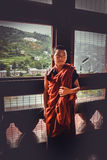 Thimphu, Bhutan - September 10, 2016:  Young novice Buddhist monk in reddish orange robes standing in front of a window. Thimphu, Bhutan - September 10, 2016 Royalty Free Stock Photos