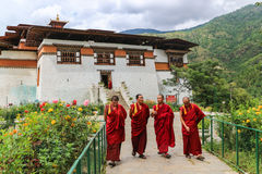 Thimphu, Butão - 15 de setembro de 2016: Quatro monges que andam no jardim de Simtokha Dzong, Thimphu, Butão Foto de Stock Royalty Free