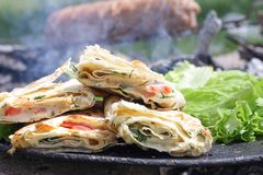 Thin Armenian lavash with tender Suluguni cheese, tomatoes, chicken and salad, grilled. Traditional Middle Eastern snack. Picnic stock image
