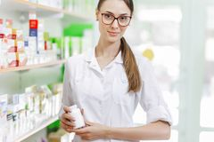A thin beautiful girl.wearing a lab coat, shows a small jar to the camera in a modern pharmacy. royalty free stock images