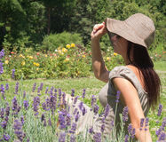 Thin beautiful woman. Fine woman sitting on the lavender field in a hot summer day Stock Images