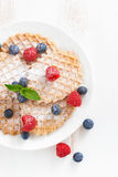 Thin Belgian waffles with berries, top view, vertical Royalty Free Stock Images