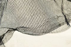 Thin black fine mesh with crumpled waves on white background und Stock Photography
