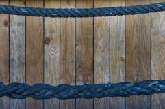 Thin blue rope as a handrail in the upper and thick rope in the. Lower third. Wooden wall in the background with selective sharpness royalty free stock photography