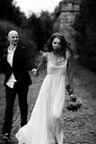 Thin bride looks gorgeous walking with groom along the path.  stock photography