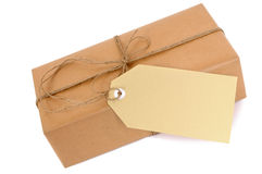 Thin brown paper package with string and gift tag or manila label isolated on white, copy space Stock Photos