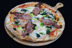 Thin crust Florentine pizza with bacon and spinach. With black background stock image