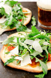 Thin crust individual pizzas with wild rocket Stock Photos
