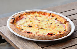 Thin crust pizza. And various type of meat on wood table Stock Image