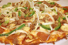 Thin Crust Pizza. This is a shot of a fresh Pizza Pie loaded with onions, green peppers, pepperoni and cheese Stock Photo