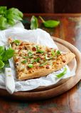 Thin-crust pizza topped with fresh basil leaves. Slice of pizza. Home made food. Italian vegetarian pizz stock photo