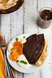 Thin delicate chocolate pancakes, rolled with fruits and cream. White wooden background. Sweet breakfast. stock photos