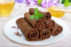 Thin delicate chocolate pancakes, rolled, laid out in a pile on a white plate Royalty Free Stock Photo
