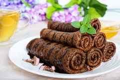 Thin delicate chocolate pancakes, rolled, laid out in a pile on a white plate and a cup of herbal tea Royalty Free Stock Photos