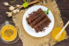 Thin delicate chocolate pancakes, rolled, laid out in a pile on a white plate and a cup of herbal tea Stock Photo