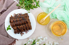 Thin delicate chocolate pancakes, rolled, laid out in a pile on a white plate and a cup of herbal tea Stock Image