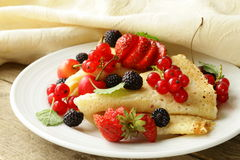 Thin dessert pancakes (crepes) with  berries Royalty Free Stock Images