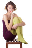 Thin fashion girl sitting on a chair. Cute Stock Image