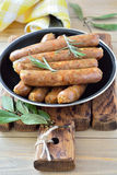 Thin fried sausages in a pan on a wooden background Stock Image