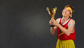 Thin, funny guy with a champion`s cup in his hands. Stock Photo