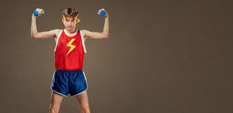A thin funny guy in sports clothes with small dumbbells Stock Image