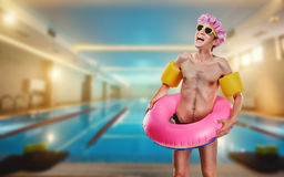 A thin, funny man naked with a ring around the pool Stock Image