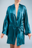 Thin girl in a blue silk robe Royalty Free Stock Photos