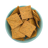 Thin gourmet snack crackers in a green bowl. Top view of a portion of gourmet teff whole grain snack crackers in a green bowl isolated on a white background Stock Images