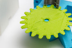 Thin green 3D printed gear with visible layers of plastic that is sustainable