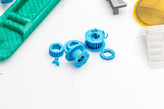 Thin green 3D printed gears with between other objects made in plastic that is sustainable Royalty Free Stock Photography