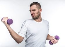 Thin guy is holding dumbbells in his hands. He is trying to gain some muscles before summers will come. He wants to. Start to go to fitness club. Isolated on Stock Photo