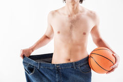 Thin guy presenting result of sport activity. Close up of slim body of young man stretching oversized jeans sideways. He is carrying basketball ball. Isolated Royalty Free Stock Images