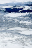 Thin Ice and Blue Water. Crack in thin ice leading to open area of blue water Stock Photos