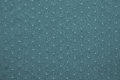 Thin knitted fabric of blue green color with blond specks. Thin texture of knitted fabric of blue green color with small blond specks for abstract backgrounds Stock Image