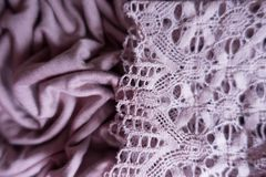Thin lace on draped pink fabric. Thin lace on draped pink viscose fabric Stock Photography